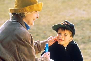 old woman applying sunscreen lotion to kid's face