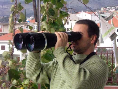 man holding huge binoculars